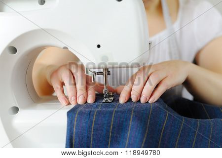 Tailoring Of Natural Wool. Woman Tailor Working On Sewing Machine.