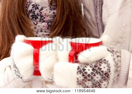 Happy Couple In Love In White Outerwear Holding Red Cups In Park In Winter