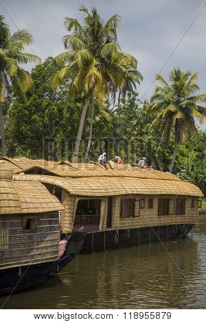 KERALA, INDIA - OCTOBER 16, 2015: Unindetified man at backwaters in Kerala India. The backwaters are an extensive network of 41 west flowing interlocking rivers lakes and canals that center around Alleppey Kumarakom and Punnamada.