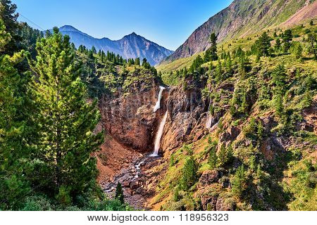 Waterfall In Forest Border In Mountains