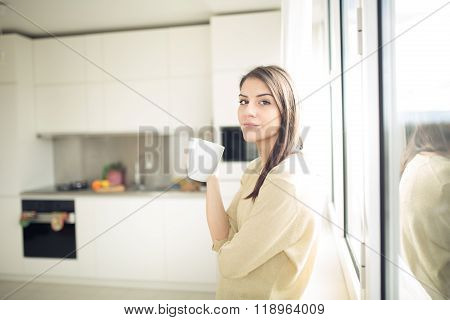 Woman enjoying,holding cup of hot beverage,coffee or tea.Looking trough the window