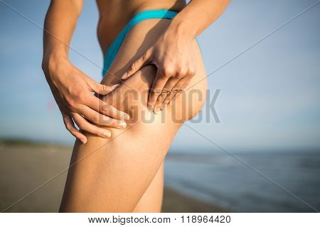 Woman is testing the skin for stretch marks and cellulite on the beach.Woman showing cellulite area