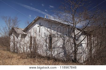 Abandoned Church sits among Weeds and Trees
