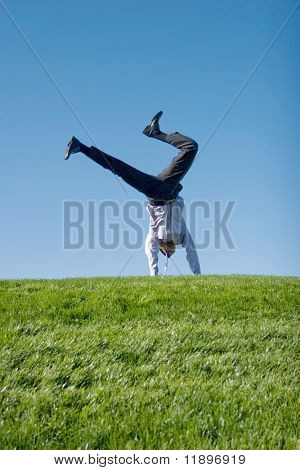 Happy businessman doing somersault on grass