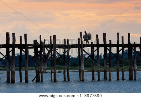 MANDALAY - September 2, 2013 : People walking on U-Bein bridge in sunset in Mandalay, Myanmar. The U-Bein bridge is the longest teak bridge in the world
