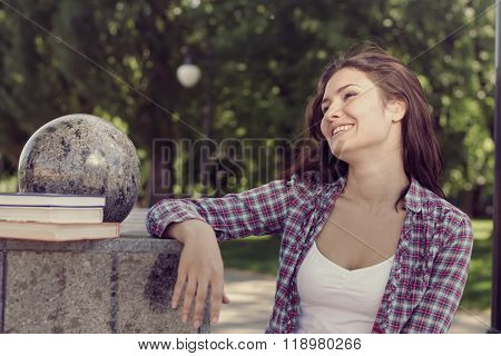 Student Standing In A Park And Laughing Merrily.