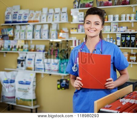 Portrait of beautiful nurse with folder at veterinary clinic.