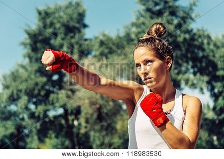Young woman doing taebo direct punch focus on eyes poster