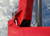 Detail of hydraulic bulldozer piston excavator arm on sky with clouds background poster