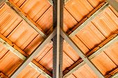 Abstract closeup of a terracotta ceramic tile roof, view from underneath building overhang,with textural and wooden structural details. poster