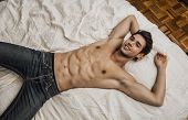 Shirtless sexy young smiling man lying alone on his bed in his bedroom, looking at camera with a seductive attitude poster
