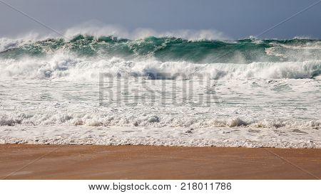Powerful and dangerous blue and aqua wave breaking near beach on Hawaii's Banzai Pipeline North Shore of Oahu.