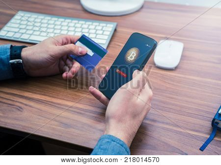 hands holding credit card and phone with cryptocurrency market. bitcoin online purchase
