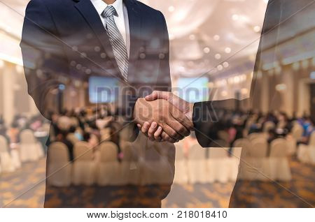 Double exposure of businessman handshake over the Abstract blurred photo of conference hall or seminar room with attendee background business agreement concept, 3D illustration
