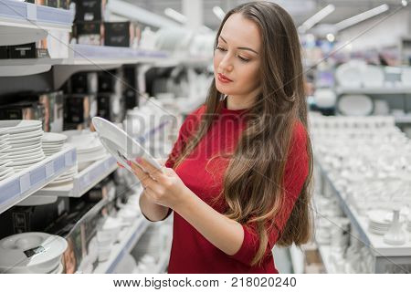 female customer choosing utensil dishes in the supermarket mall. good housewife