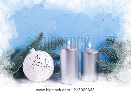 Christmas background. Silver candles branches fur tree and white ball on white background against blue wall. Selective focus is on candles. Drawn snow frame.