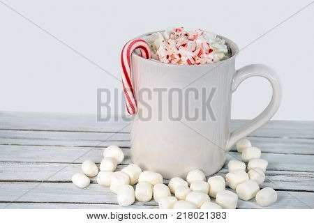 hot chocolate mug with marshmallows and whipped cream with Christmas candy cane on whitewashed wood