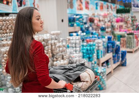 Christmas shopping - woman shopper with cart walking at supermarket store with holidayschristmas background