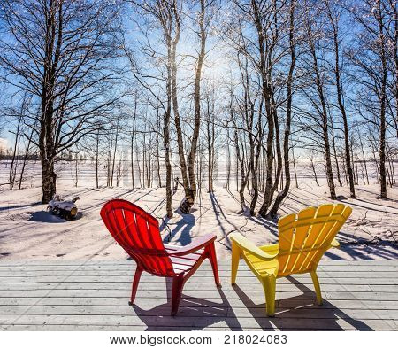 Comfortable red and yellow plastic chaise lounges for relaxing in forest. Sunset in the Arctic. The sun shines low over the horizon. The concept of extreme and ecotourism tourism