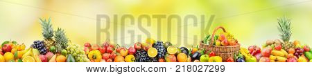 Fresh healthy fruits and vegetables in basket on natural blurry multicolored background. Free space for text.