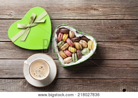 Colorful macaroons in Valentines day heart shaped gift box and coffee cup on wooden table. Top view with copy space