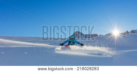Young man snowboarder running downhill in powder snow, Alpine mountains. Winter sport and recreation, leasure outdoor activities.