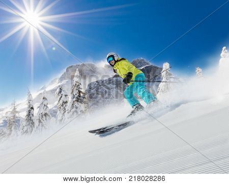 Young woman skier running down the slope in Alpine mountains. Winter sport and recreation, leasure outdoor activities.