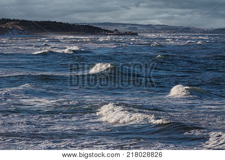Waves rolling in along the shoreline of Cavendish beach in Prince Edward Island National Park, PEI, Canada.