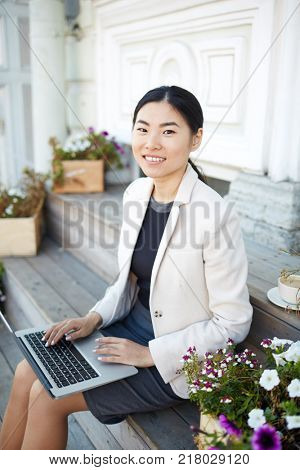 Young Asian female with laptop sitting on stairs in urban environment