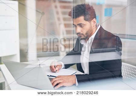 Busy young analyst looking through online statistics and writing some things in notebook
