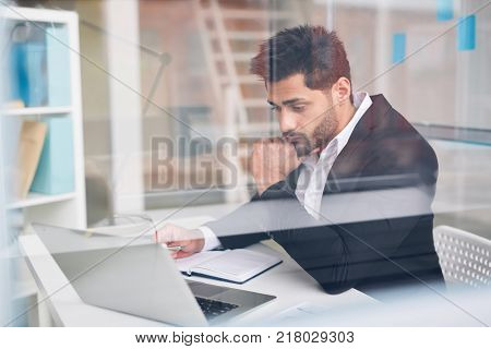 Young financier concentrating on working over online project or reading data
