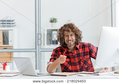Young successful designer with pencil pointing at you while sitting by workplace between open laptop and computer monitor