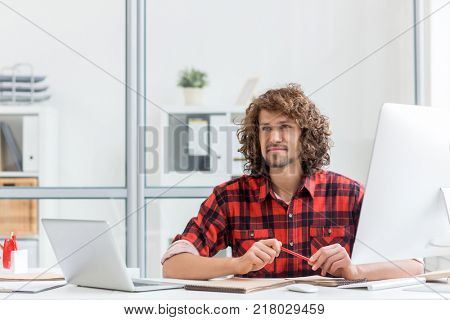 Young curly designer thinking of new ideas for his working project