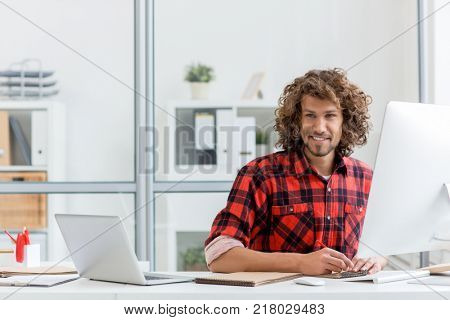 Young businessman with pencil sketching in notepad by his workplace