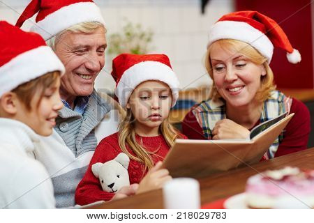 Cute girl and her elder brother reading tales on xmas evening with their grandparents near by