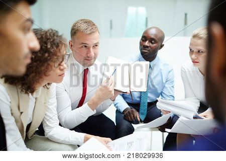 One of intercultural managers pointing at page of notebook with points of his business plan