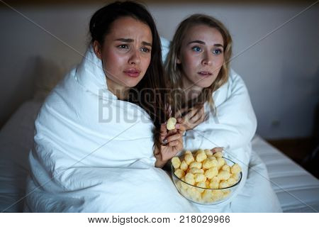 Emotional girls wrapped into blanket watching drama movie with tense expression on their faces
