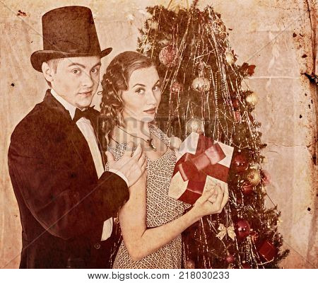 Christmas nostalgy couple on party near Christmas tree take gift box and Xmas presents in 1910-1940. Happy family on holiday. Man in cylinder hat and tail-coat.