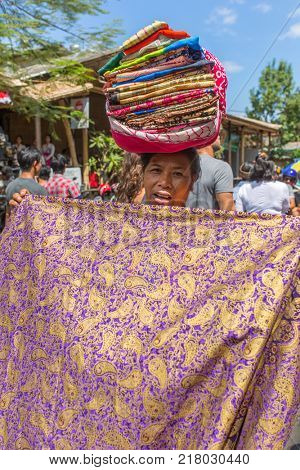Bali, Indonesia - August 20, 2016: Balinese vendor displays sarongs for sale to tourist during public cremation in Ubud, Bali, Indonesia.