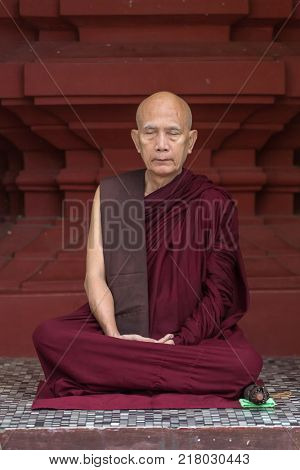 Yangon, Myanmar - September 27, 2016: Portrait of unidentified buddhist monk meditating in Shwedagon pagoda in Yangon, Myanmar