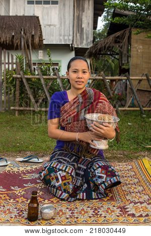 Vang Vieng, Laos - January 21, 2017: Unidentified lao woman wait for Buddhists monks to give them alms.