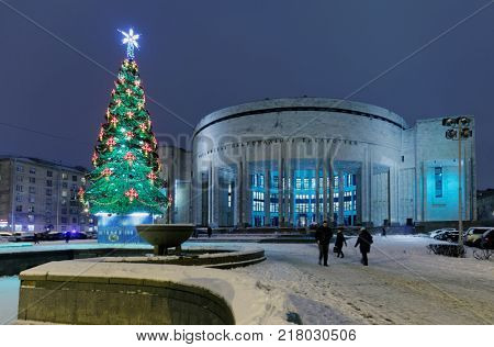 ST. PETERSBURG, RUSSIA - DECEMBER 1, 2017: People at the Christmas tree neat the National Library of Russia. Founded in 1795, now the library houses about 36 millions items