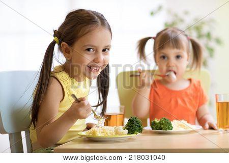 kids eating healthy food in kindergarten, nursery or at home