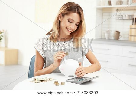 Young woman putting coin into piggy bank indoors