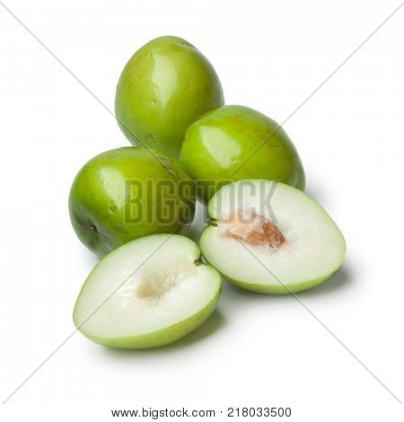 Fresh green whole and half Ambarella fruit with a fibrous pit on white background