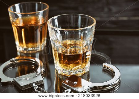 Glasses with handcuffs on table. Alcohol dependence concept