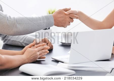 Senior couple meeting with consultant in office. Young woman and senior man shaking hands, closeup