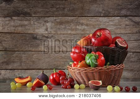 Basket with different fruits and vegetables against wooden background