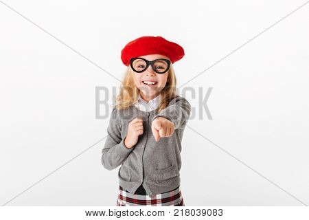 Portrait of a happy little schoolgirl dressed in uniform grimacing and pointing finger at camera isolated over white background