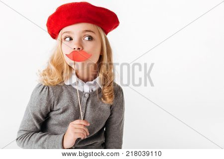 Portrait of a pretty little schoolgirl dressed in uniform grimacing and looking away at copy space isolated over white background